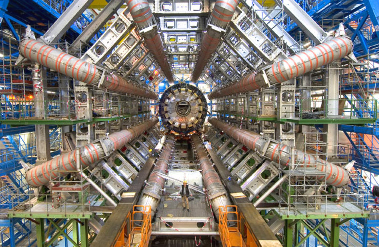 A hardhat worker is dwarfed by the inner workings of the Large Hadron Collider's ATLAS detector, deep beneath the French-Swiss border.