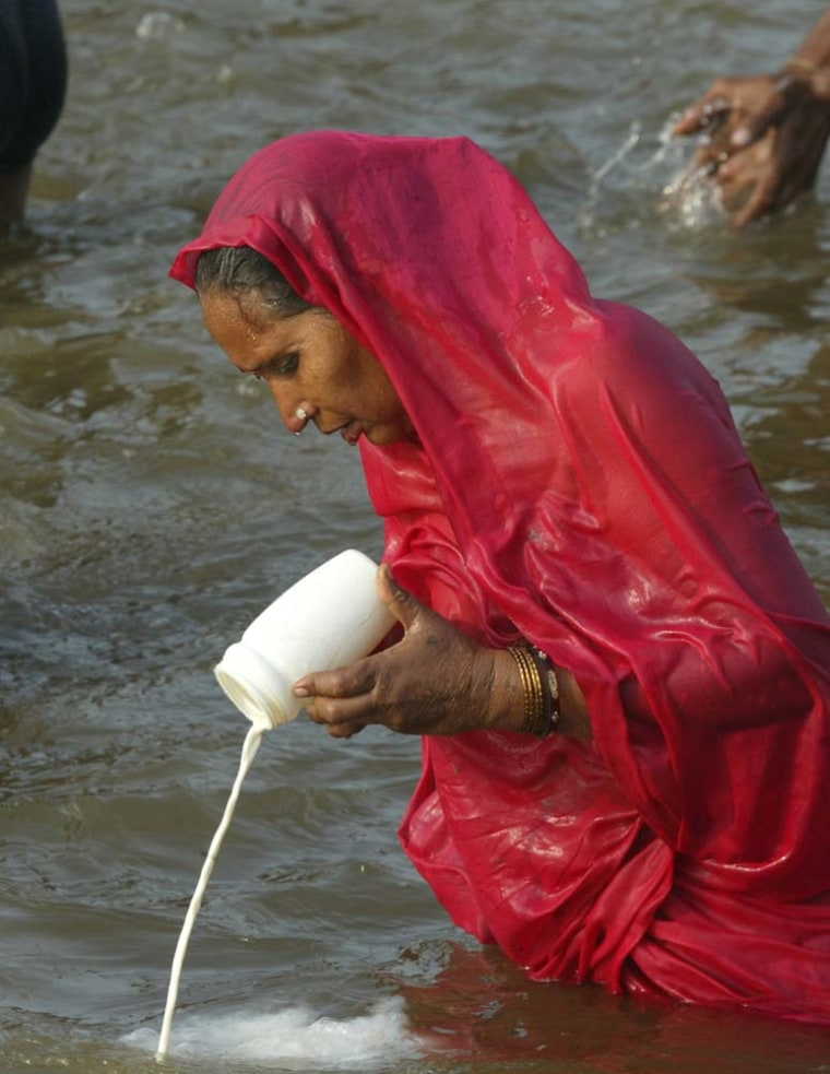 """A Hindu devotee performs a ritual by pouring milk into the river after taking a holy dip on the occasion of """"Poush Poornima"""" at the """"Ardh Kumbh Mela"""" or Half Grand Pitcher festival at Sangam in Allahabad, India, Wednesday, Jan. 3, 2007. Ash-smeared and naked Hindu saints led millions of devotees Wednesday in a pre-dawn holy dip in frigid temperatures at the confluence of three major rivers in north India, starting a week long pilgrimage to wash away their sins."""