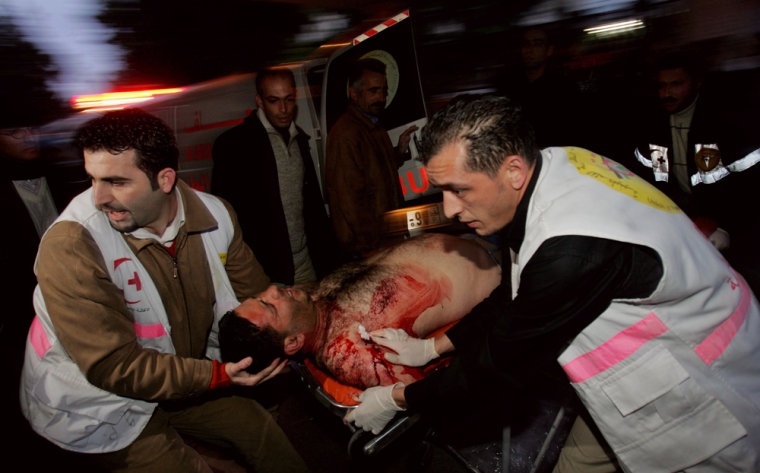 Palestinians carry a wounded man for treatment after he was injured Thursday during an Israeli army operation in the West Bank city of Ramallah.