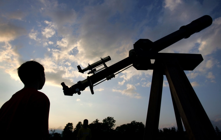 """Ten-year-old Matthew Hubbard looks at Jim Podpolucha's homemade achromatic refractor telescope during a star party at Cherry Springs State Park in Pennsylvania. The statehasset asideCherry Springs as a """"dark sky"""" park, one of a small but growing number of parks around the country dedicated to preserving the night sky."""
