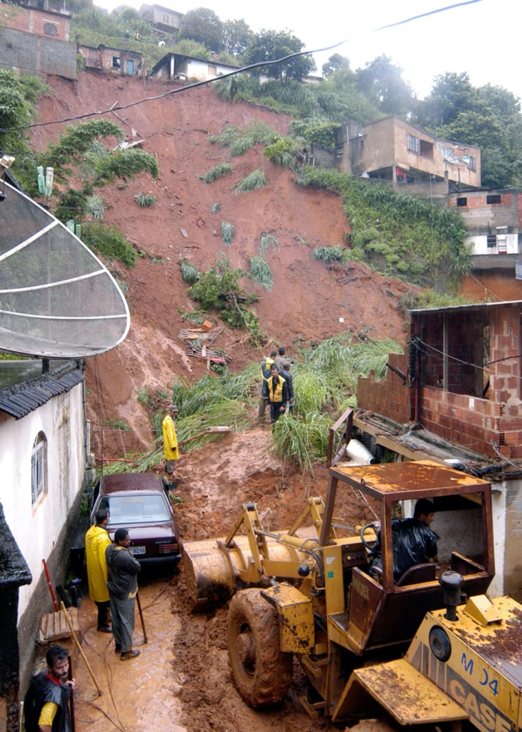 Firefighters look for the remains of three missing people in Petropolis, Brazil, on Thursday.