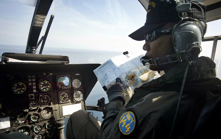 A helicopter pilot checks his map during