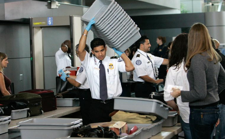 A TSA agent is seen getting trays for travelers to go through the metal detectors at the security gate at Oakland International Airport in Oakland, Calif.