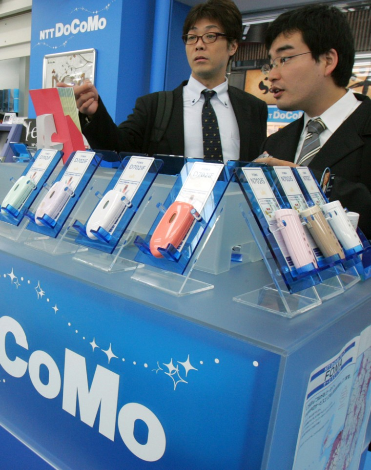 Japanese businessmen look at brochure at the NTT DoCoMo's sales counter at an electric and electronic discount chain store in Tokyo. Japan's largest mobile phone carrier will upgrade its wireless network to make its data transmission hundreds of times faster, enabling subscribers to watch high-quality video just as they can over fiber-optic cables.