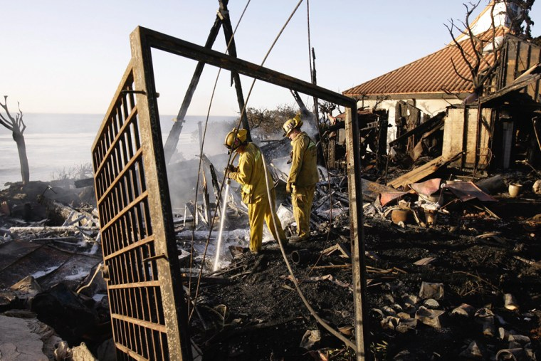 Los Angeles County firefighters hit hot spots on Tuesday at one of the four mansions in Malibu, Calif., destroyed during a wildfire Monday night.