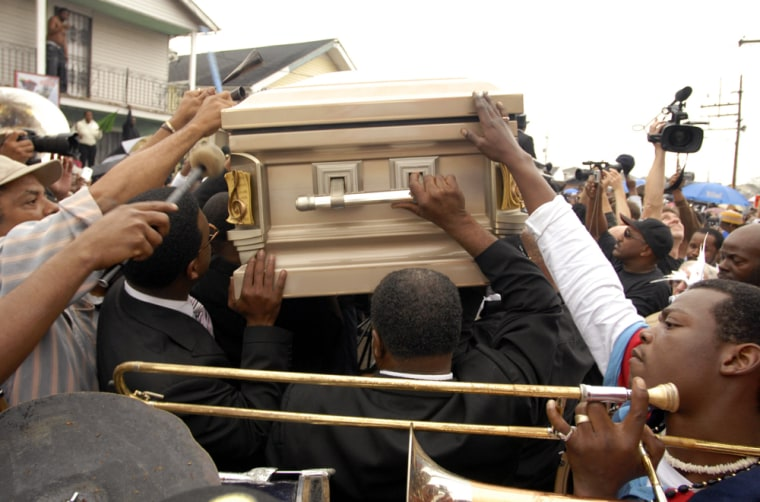 Mourners carry the casket of a 25-year-old man killed late last month.