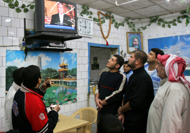 Iraqis watch President Bush's televised address to the United States, in Basra, Iraq.