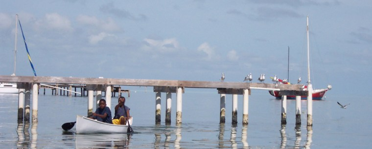 Unidentified boys are seen maneuvering a kayak past a pier and toward the beach of Caye Caulker, a sleepy resort island in Belize.