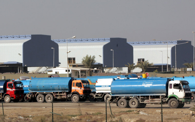 Trucks drive in front of an aluminum smelting plant to fill up with fresh water distilled from gulf seawater in Dubai, United Arab Emirates. Residents of the small desert isle outpace Americans in terms of energy consumption, says the World Wildlife Fund.