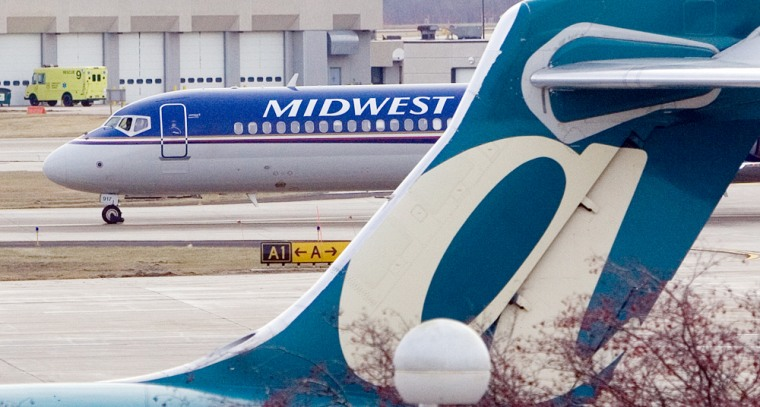 A Midwest plane taxis past a parked AirTran plane at Gen. Mitchell International Airport in Milwaukee. AirTran Holdings Inc. appealed directly to shareholders Thursday with its sweetened offer of about $345 million in cash and stock for rival Midwest Air Group Inc.