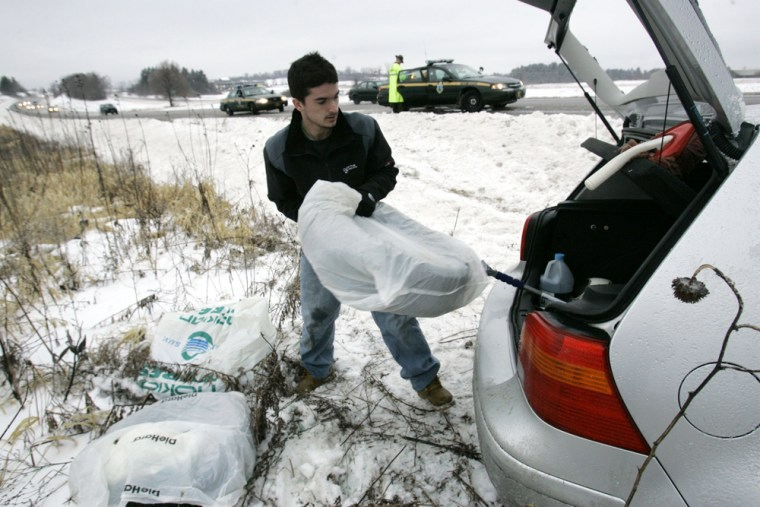 Anthony Yantz loads snow tires into his car on Monday in South Burlington, Vt., after the car slid off the highway.
