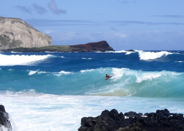 A boogie boarder catches a wave off Makapu'u Beach, with Rabbit Island in the distance, on Oahu, Hawaii.