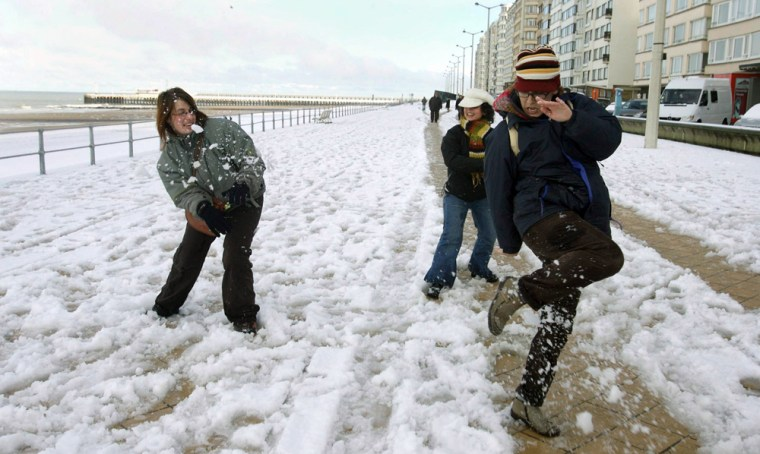 People enjoy the first snow on the beach