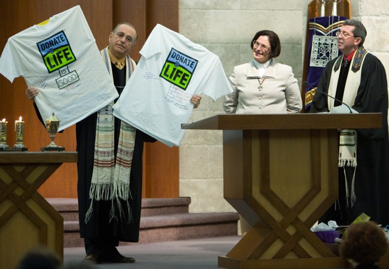 Reform Rabbi Andrew Bossov, right, and Methodist Rev. Karen Onesti, center, look on while Rabbi Emeritus Richard Levine shows off shirts to the congregation during a special blessing and ceremony in Mount Laurel, N.J., Friday, Jan. 19, 2007. Bossov was diagnosed with kidney failure nearly 10 years ago and Onesti donated one of her kidneys to him on Tuesday.