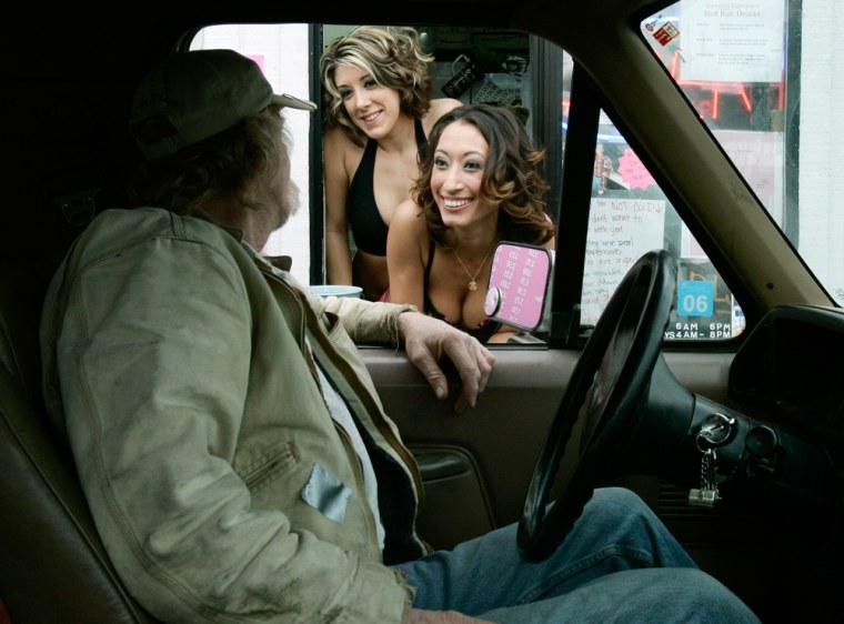 Baristas Toni Morgan, left, and Candice Law chat with customer Phil Sheridanat the Cowgirls Espresso drive-through in Tukwila, Wash.