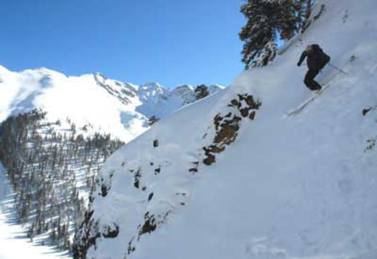 Skiers standing at the top of the Two Smokes chute are always with a guide — this part of Silverton Mountain is guide-only. But even a guide won't make this 53-degree rock funnel any less challenging.