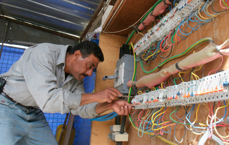 An employee of a private generator company, which supplies electricity to most Baghdad residents, works on circuit breakers in Baghdad, inMarch 2006. The new audit shows electrical output still averages below pre-war levels.