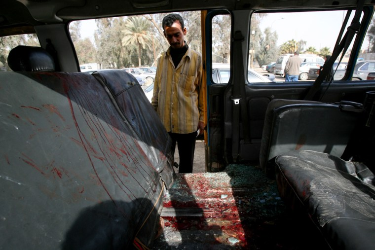 A man checks the interior of a mini bus carrying pilgrims that came under attack in the al-Amil neighborhood of Baghdad on Tuesday