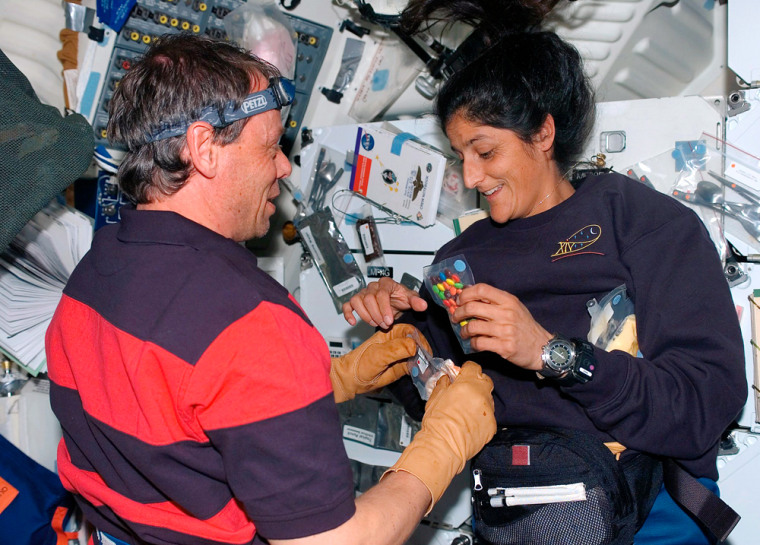 European Space Agency astronaut Christer Fuglesang of Sweden and Sunita Williams, both STS-116 mission specialists, enjoy light moment on middeck of space shuttle Discovery