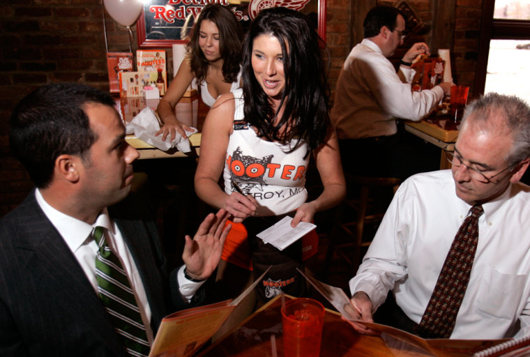 A Hooters waitress takes lunch orders from Bill Collins, left, and Dave Sanback in Troy, Mich., on Tuesday.