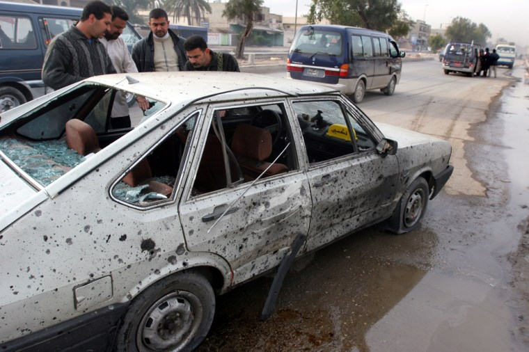 Iraqis gather around a car damaged in a bomb blast in Baghdad on Monday.