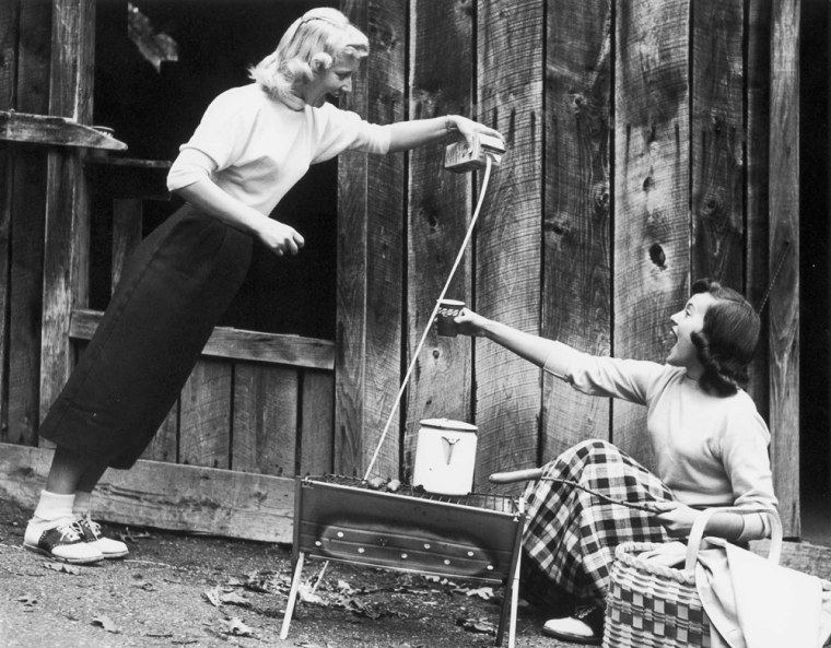 """This 1957 publicity photo shows milk seemingly being poured at an angle, demonstrating the """"mystery"""" of The Wonder Spot in Lake Delton, Wis."""
