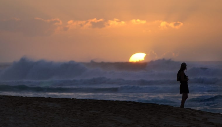 A women watches the sun set behind swellls of waves rolling to the shore at Sunset Beach on the north shore of Oahu.