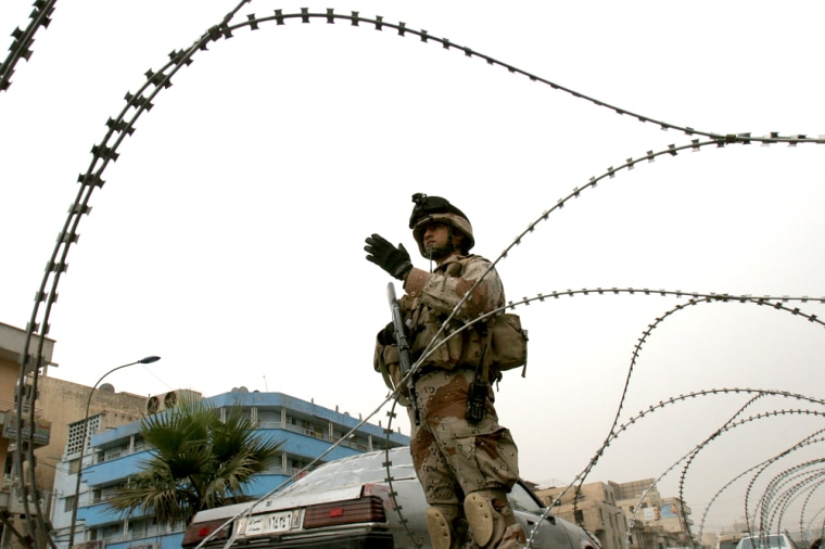 Razor wire frames an Iraqi soldier directing traffic Tuesday in Baghdad. The U.S.-Iraqi security operation aims to curb sectarian violence.