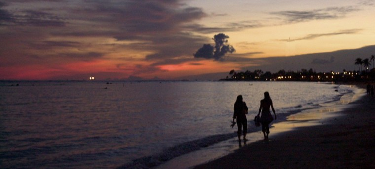 People walk along the beach as the sun sets on Waikiki.