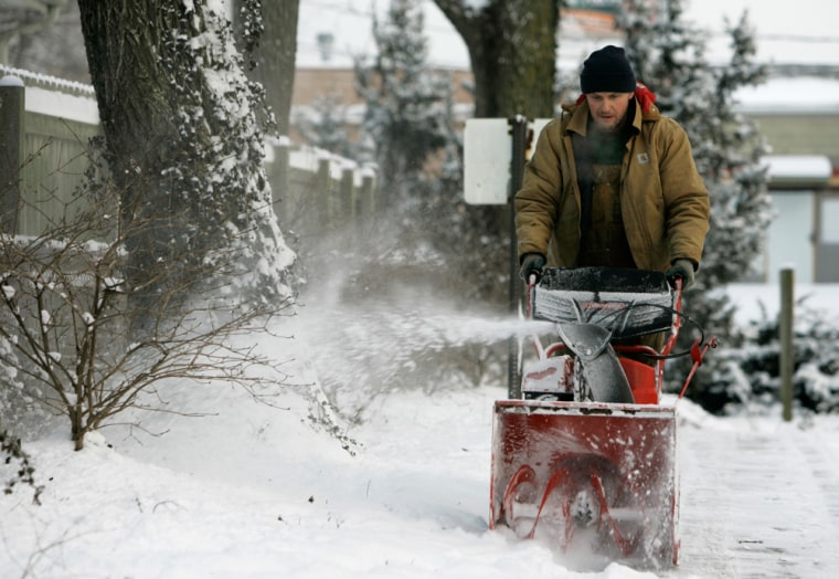 John Silvers of Columbus, Ohio, uses a snow blower to clear the sidewalk onWednesday.
