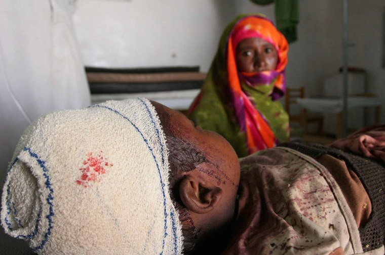 A woman sits beside her injured son inside the hospital in Adre bordering Sudans Darfur region