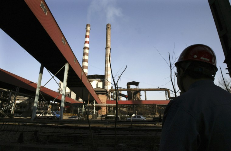 A worker looks at the Shougang Iron and Steel Group plant in Beijing