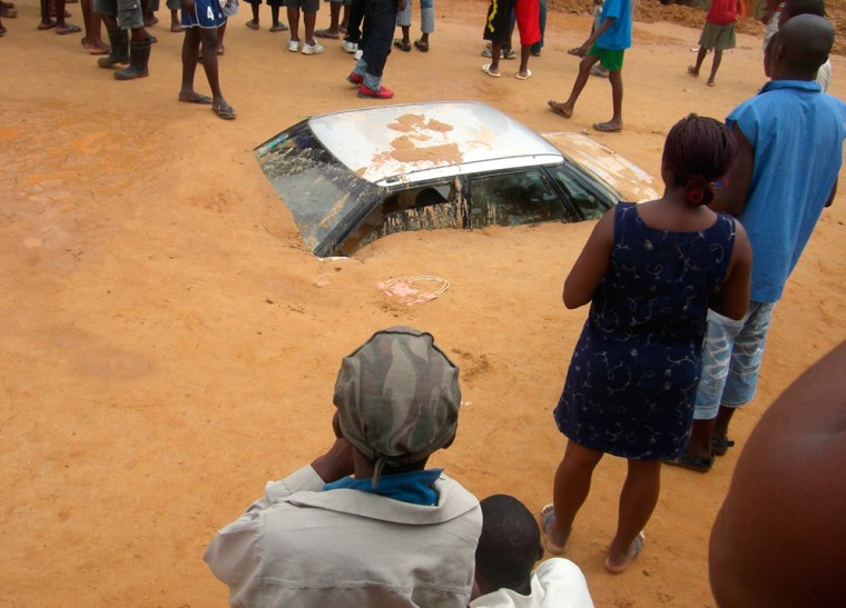 Residents of Luanda crowd around cars buried under mud after days of torential rains