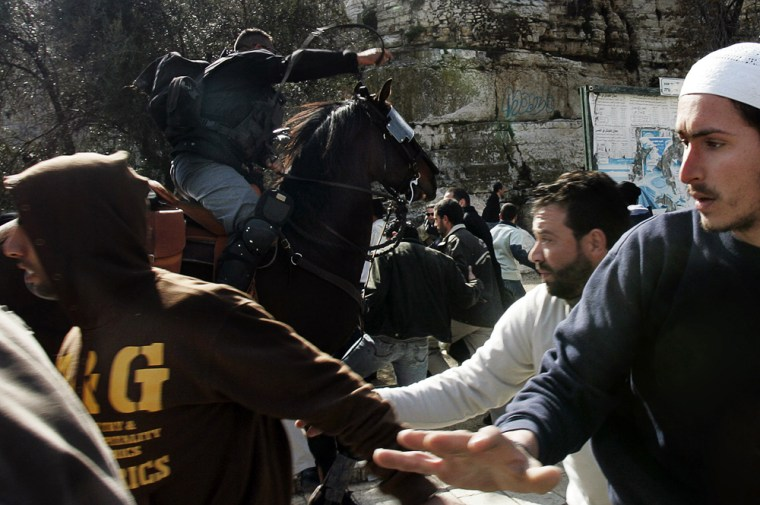 Palestinian men run as an Israeli police