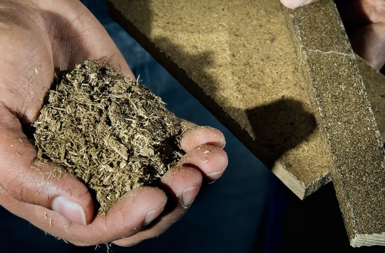 Omar Faruk, post-doctoral assistant at Michigan State University holds dried manure, left, that is processed into building materials such as particle board, center, and extruded lumber, right,.