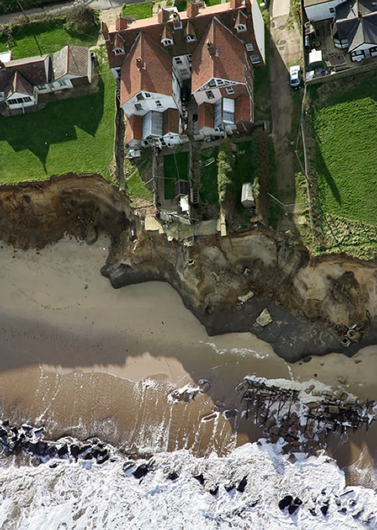 Storms have eaten away at beach property in Happisburgh, England. The Cliff House,top center, nowstands only about 15 feet from the edge of the cliff.A garage, several bungalows and a small road behind the house were taken out by the erosion.