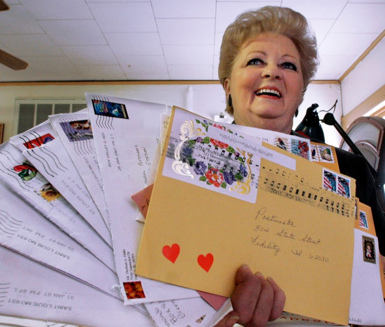 Postmaster Peggy Ruyle displays a handful of mailings sent her way from around the globe for postmarking in advance of Valentine's Day in Fidelity, Ill.