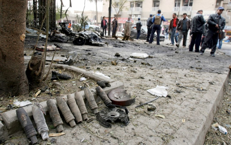 Artillery shells used to make a car bomb lay gathered by Iraqi police near the scene of an explosion in central Baghdad, Iraq, on Saturday.