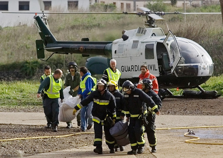 Civil Guard officers and firefighters carry plastic bags with the remains of the two persons found dead in the underground tunnel complex.