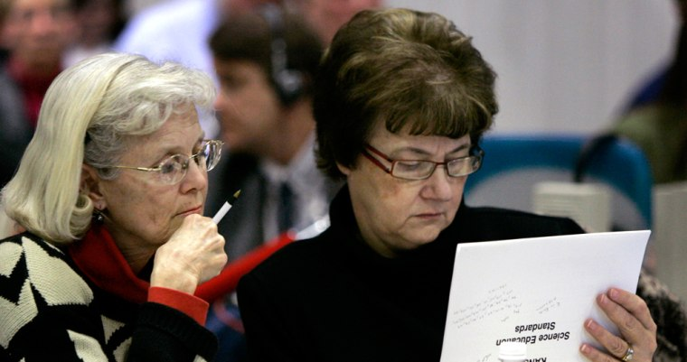 Kansas Board of Education members Kathy Martin, left, and Sally Cauble look over the new science standards approved Tuesdayin Topeka.