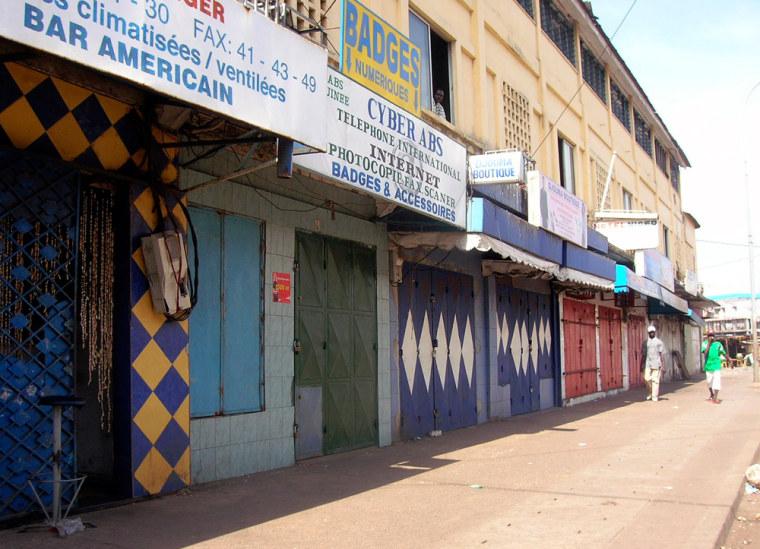 Two men walk on an empty street in front of closed shops in Conakry