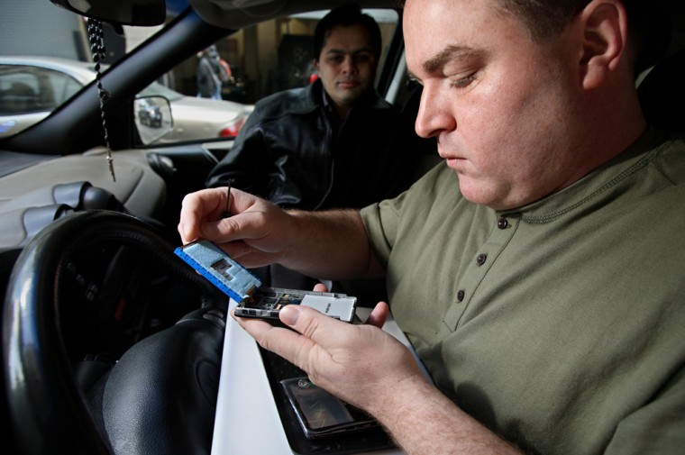 Demetrios Leontaris fixes iPods in the front seat of his SUV often as the owner looks on.
