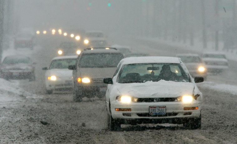 Slowed by a storm that could dump a foot of snow,traffic heads toward downtown Columbus, Ohio, on Tuesday.