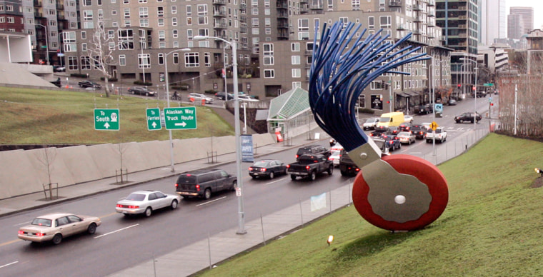 """The 19-foot tall """"Typewriter Eraser, Scale X,"""" by Claes Oldenburg and Coosje van Bruggen stands in view of traffic passing on nearby Elliott Avenue at the Seattle Art Museum's new sculpture park."""
