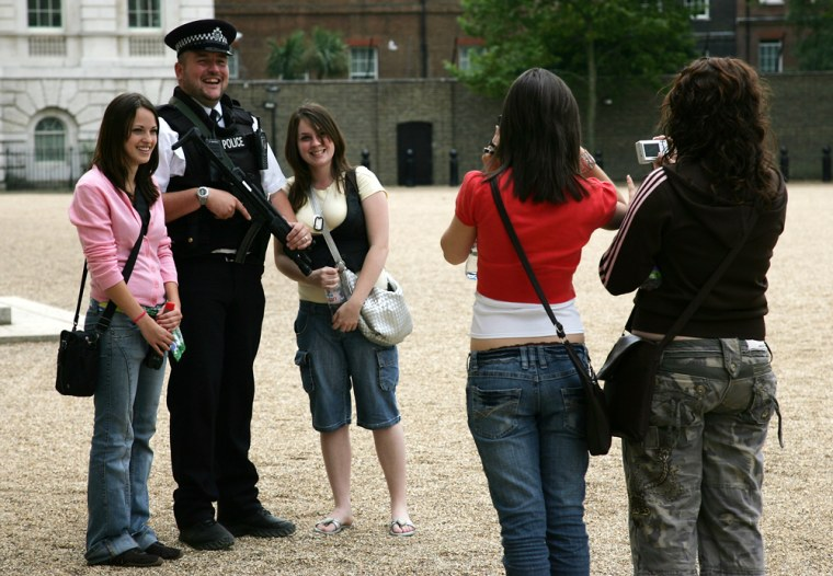 Unidentified tourists pose next to an armed British police officer as he stands guard at Horse Guards Parade in London.