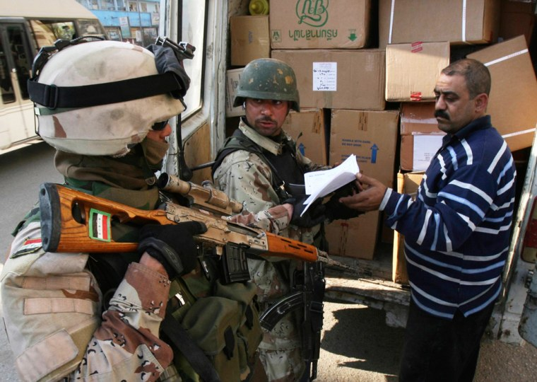 Iraqi soldiers check boxes inside a truck at a checkpoint in Baghdad