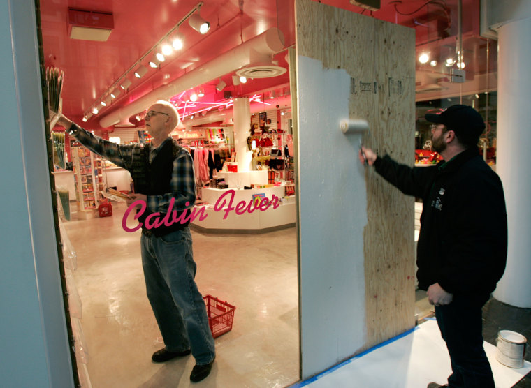 Aworker paints a sheet of plywood as a temporary repair to a plate glass window that was shot out as a store employee restocks a gift store in Trolley Square mall onWednesday.