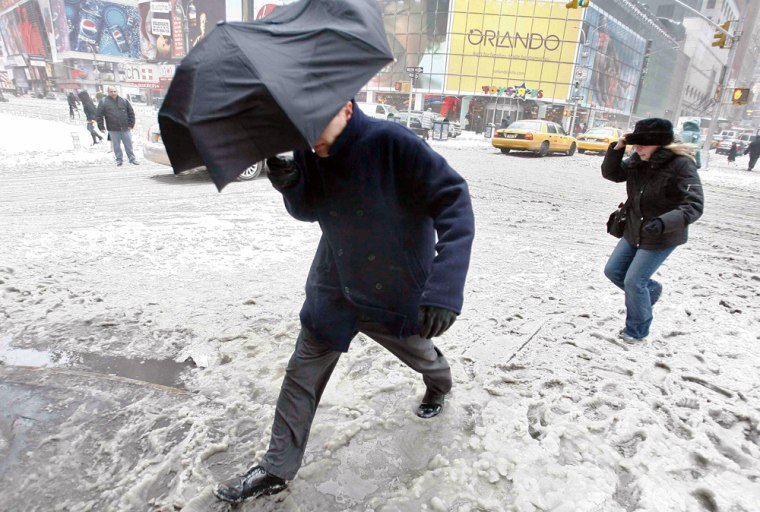 Pedestrians walk way through Times Square during a snow in New York