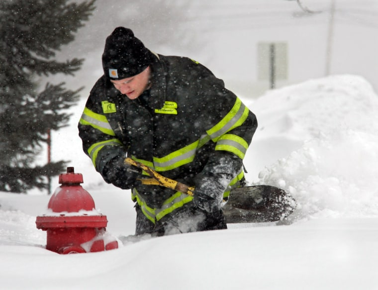 Firefighter Glen Eisenhardt clears snow from a hydrant in Olmsted Falls, Ohio, on Wednesday. More than a foot of snow fell on the Cleveland suburb.