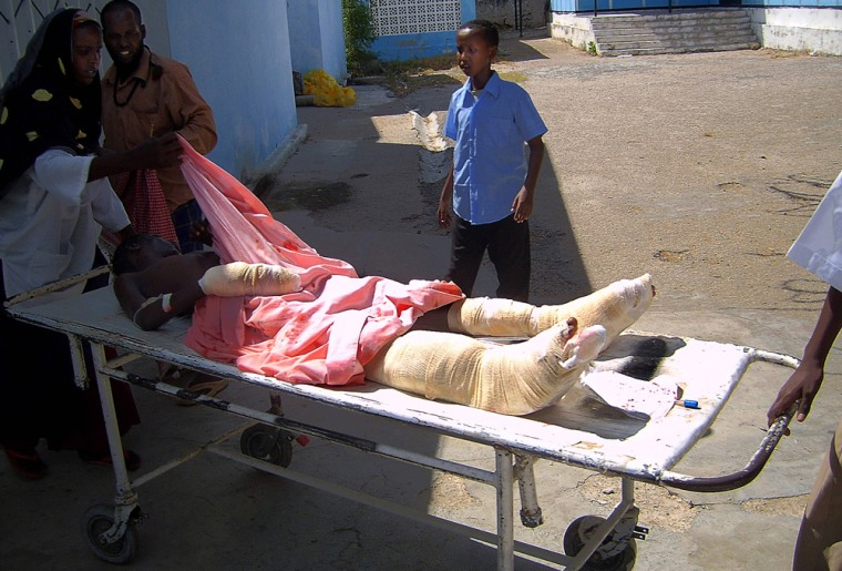 A wounded Somali youth is wheeled away o